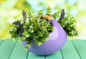 Kruka med blommor på ett träbord i naturen bakgrunden — Stockfoto