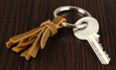 Key with leather trinket on wooden background — Stock Photo