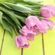 Beautiful bouquet of purple tulips on green wooden background — Stock Photo #25187797