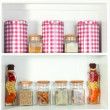 Beautiful white shelves with spices in glass bottles — Stockfoto #25188295