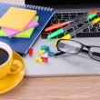 Laptop with stationery and cup of coffee on table — Stock Photo #25188375