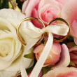 Wedding rings tied with ribbon on rose background — Stock Photo