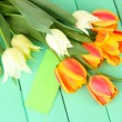 Beautiful white and orange tulips on color wooden background — Stock Photo #25189641