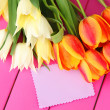 Beautiful white and orange tulips on color wooden background — Stock Photo #25189681