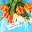 Beautiful white and orange tulips on color wooden background — Stock Photo #25189703