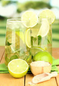 Glasses of cocktail with lime and mint on wooden table on bright background — Stock Photo