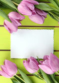 Beautiful bouquet of purple tulips and blank card on green wooden background — Stock Photo