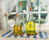 Original glass bottles with salad dressing on wooden table on window background — Stock Photo