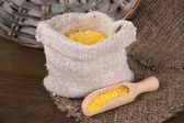 Grains in sack on wooden background — Stockfoto