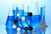 Molecule model and test tubes with liquid on blue background — Stock Photo