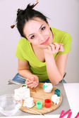 Young pretty woman working on clay sculpture, on gray background — Stock Photo