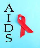 Aids awareness red ribbon on blue background — Stock Photo