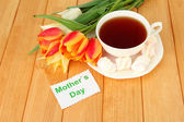 Composition of tulips and cup with some drink, on wooden background — Stock Photo