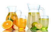 Orange and lemon lemonade in pitchers and glasses isolated on white — Stock Photo