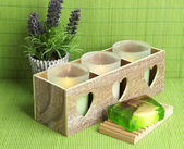 Candles in wooden candlestick, lavender and soap, on green mat — 图库照片