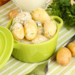 Tender young potatoes with sour cream and herbs in pan on wooden table close-up — Stock Photo