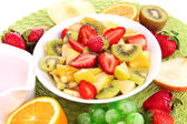 Useful fruit salad of fresh fruits and berries in bowl on napkin isolated on white — Stock Photo