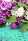 Beautiful lilac flowers, on color wooden background — Stock Photo