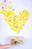 Papier gelb schmetterling in form von herzen fliegen buch — Stockfoto