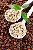 Grãos de café verdes e marrons com folhas — Fotografia Stock
