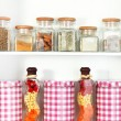 Beautiful white shelves with spices in glass bottles — Stock Photo