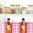 Beautiful white shelves with spices in glass bottles — Photo