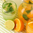Orange and lemon lemonade in pitchers and glasses on wooden table close-up — Foto de Stock