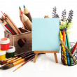 Pencils in wooden crate, paints, brushes and easel, isolated on white — Stock Photo #25317189