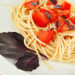 Spaghetti with tomatoes and basil leaves close-up — Stock Photo #25317205
