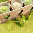 Wooden candlestick with candles and bamboo, on green mat — Stock Photo