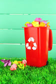 Recycling bin with papers on grass on light blue background — Stockfoto