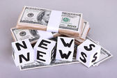 """White paper cubes labeled """"News"""" with money on grey background — Stockfoto"""