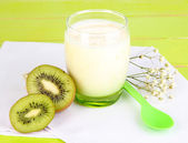 Delicious yogurt with kiwi in glass on wooden table close-up — Stock Photo