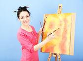 Pittore giovane e bella donna al lavoro, sul colore di sfondo — Foto Stock