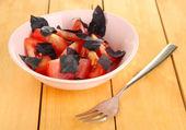 Salát z čerstvých rajčat s bazalkou listy v misce na dřevěné pozadí — Stock fotografie