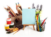 Pencils in wooden crate, paints, brushes and easel, isolated on white — Stock Photo