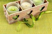 Drewniany świecznik z świece i bambusa, na zielony mat — Zdjęcie stockowe