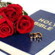 Royalty-Free Stock Photo: Wedding rings with roses on bible isolated on white