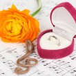Treble clef, flower and box holding wedding ring on musical background - Photo