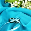 Wedding rings tied with ribbon on cloth background — Stock Photo