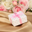 Beautiful gift on flowers background — Stock Photo