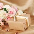 Beautiful gift on flowers background — Stock Photo #25326509