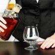 Barman hand with bottle of cognac  pouring drink into glass, on bright background - Stock Photo