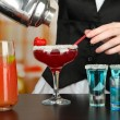 Stock Photo: Barmen hand with shaker pouring cocktail into glass, on bright background