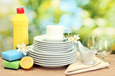 Empty clean plates, glasses and cups with dishwashing liquid, sponges and lemon on wooden table on green background — Stock Photo