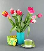 Beautiful tulips in bucket with gifts and cup of tea on grey background — Stock Photo