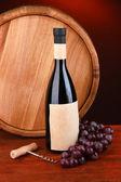 Skład korkociąg i butelka wina, winogron, drewniane beczki na drewnianym stole na ciemnym tle — Zdjęcie stockowe