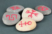 Fortune telling with symbols on stones on grey background — Stock Photo