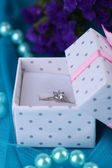 Flowers and engagement ring on blue cloth — Stock Photo