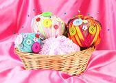 Colorful buttons and multicolor wool balls in wicker basket, on color fabric background — Stock Photo
